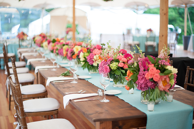 long farm tables with light blue runners and vibrant flowers